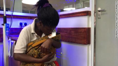 Lilian Matchaya holds her daughter, Abigail, praying for her to get better.