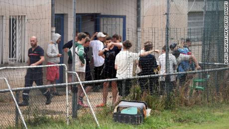 German teenagers from a summer camp stand in front of a rescue center after being evacuated from a flooded campsite.