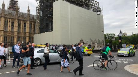 Commuters look on after man crashes vehicle near Westminster in London