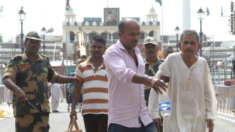 Indian officials help Gajanand Sharma cross over the India-Pakistan Wagah Border Post on August 13.