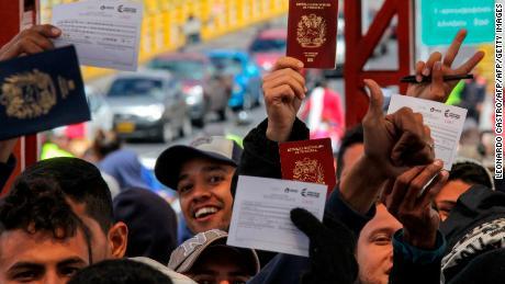 Venezuelan citizens wait in line to cross to Ecuador at the Rumichaca international bridge in Ipiales, Colombia, on August 11, 2018.