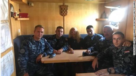The woman sits with members of the Croatian Coast Guard.