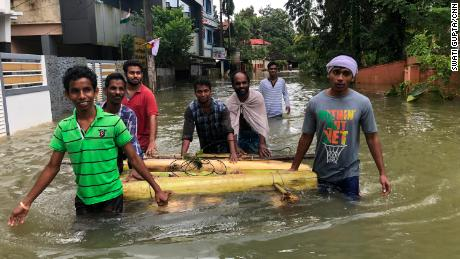 Rescuers wade through the floodwaters.
