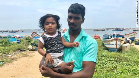 Fisherman Arun Michael with his daughter, Andrea Marie, after he and other rescuers evacuated more than 1,500 people over three days.