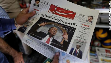 A man takes a glance at a newspaper with a picture of US President Donald Trump on the front page, in Tehran on July.