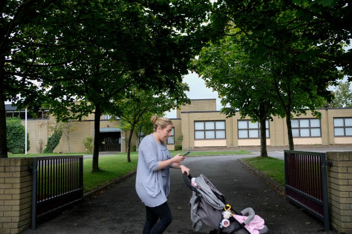 A woman passes one of three Catholic primary schools on Leixlip's Green Lane.