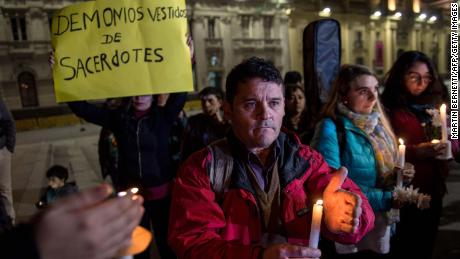 """A demonstrator holds a placard reading """"Devils Disguised as Priests"""" during a protest against the sexual abuse scandal in Santiago, Chile."""