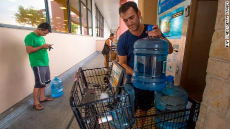 Wenkai He, left, waits to fill a 3-gallon water jug while Alex Krivoulian finishes filling three jugs at a Safeway store in Honolulu on Wednesday.