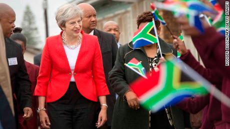 Britain's Prime Minister Theresa May (L) is greeted by schoolchildren waving British and South African flags.