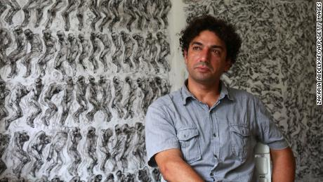 Syrian artist and painter Najah al-Bukai sits in front of his drawings which he used to document torture and the dead at Syrian prisons.