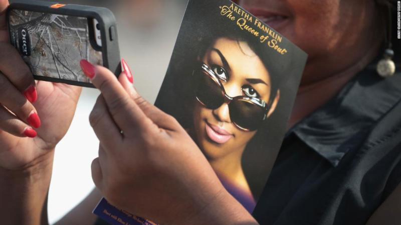 A fan takes a photograph while waiting to view Franklin's body.