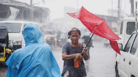 A woman is lashed by rain in Manila as authorities warn millions of potentially heavy destruction.