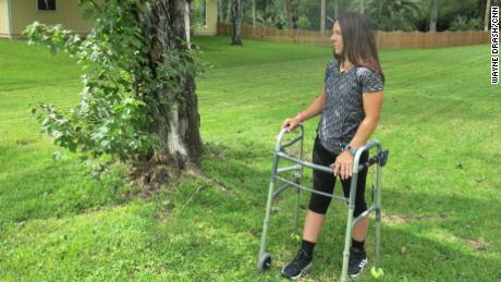 "Thomas stands next to the red maple where the truck she was driving came to a halt. ""The stimulator is facilitating my movement,"" she says, ""but my strength is coming from within."""