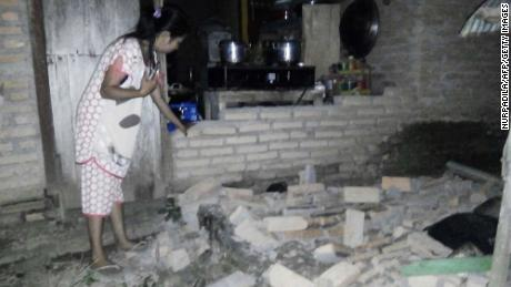A resident is seen beside the collapsed brick wall of her house at Tobadak village in Central Mamuju, western Sulawesi province, on September 28 after a strong earthquake hit the area.