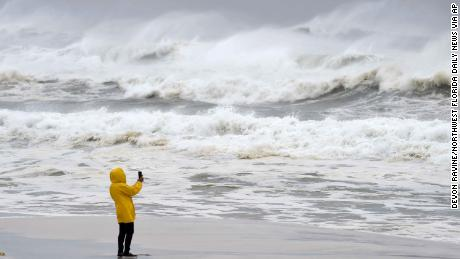 An unidentified person takes pictures Wednesday on Okaloosa Island in Fort Walton Beach.