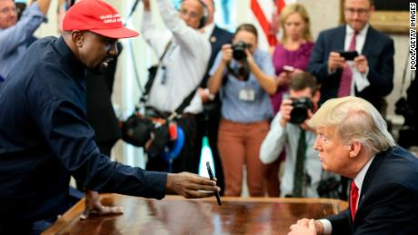 Rapper Kanye West , left, shows a picture of a plane on a phone to U.S. President Donald Trump during a meeting in the Oval office of the White House on October 11, 2018 in Washington, DC.