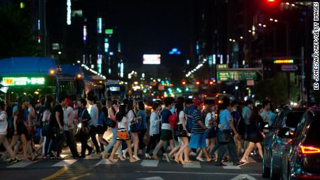 Pedestrians cross a road in the Gangnam district of Seoul. South Korea has some of the longest working hours in the world.