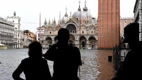 Tourists take pictures in the flooded St Mark's Square during a high-water alert in Venice on October 29, 2018.