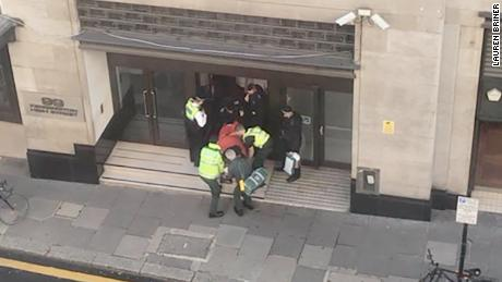 A person is carried out of a building on a stretcher in Derry Street, Kensington, on Friday.