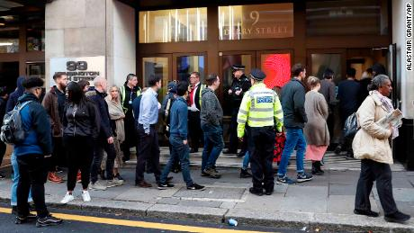 Police officers and security watch as people re-enter a building after a stabbing incident in Derry Street on Friday.