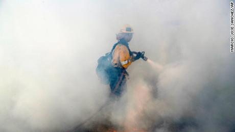 A firefighter fights wildfire in Agoura Hills, Los Angeles County, on Friday.