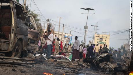 People gather in the street amidst the rubble of car bombs in Mogadishu, Somalia.
