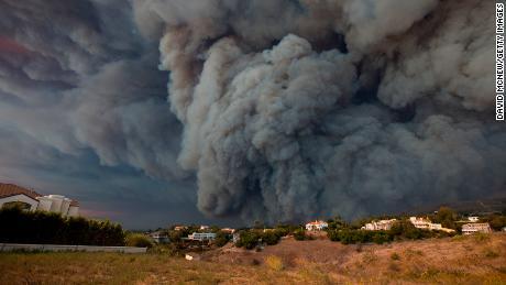 Un panache de fumée massif, alimenté par des vents violents, s'élève au-dessus du feu de Woolsey vendredi à Malibu.