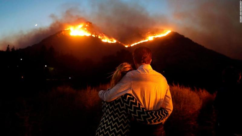 Roger Bloxberg and his wife, Anne, hug as they watch a wildfire on a Los Angeles hilltop on Friday, November 9.
