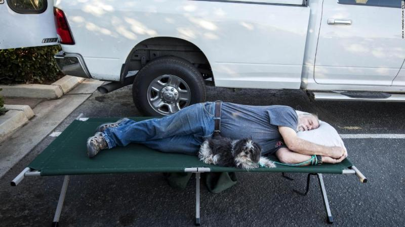Doug Thomas and his dog Hanna rest November 9 while they await word if they can return to their Malibu Lake home.