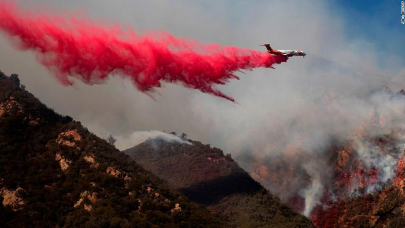 A plane drops fire retardant on November 11 on a burning hillside in Malibu.
