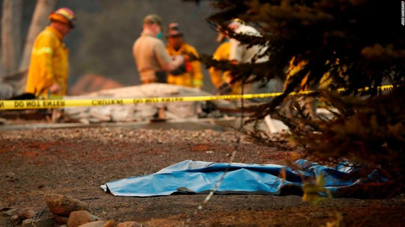 A bag containing human remains lies on the ground as officials continue to search for victims at a burned-out home in Paradise on November 11.