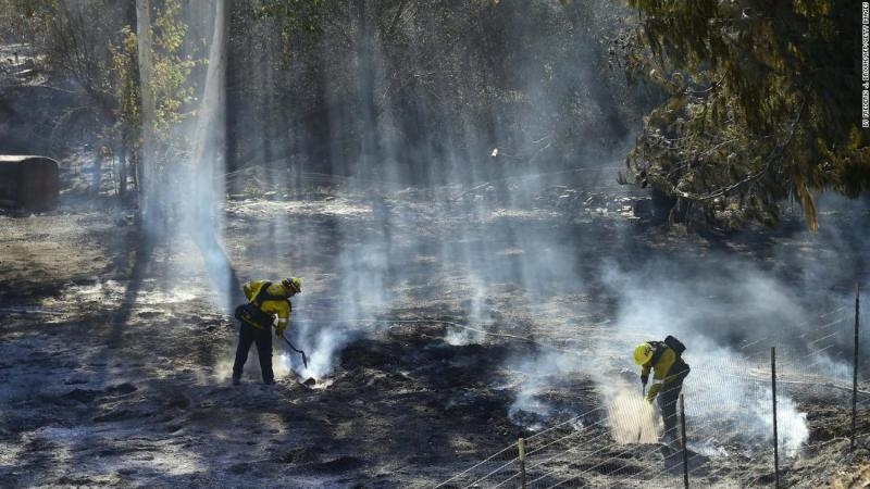 Firefighters douse burning embers off a canyon road which cuts across the mountains to Malibu.