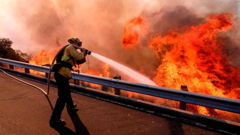 A firefighter battles a fire on November 12 along the Ronald Reagan Freeway in Simi Valley.