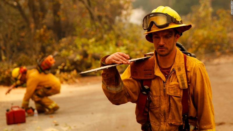 Shawn Slack carries a chainsaw on November 12 after trees burned in the Camp Fire in Paradise.