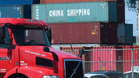 A container delivery truck drives past stacked piles of shipping containers at the Port of Long Beach.