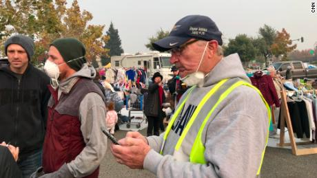 Rob Busick, left, wearing a mask, and Guido Barbero, right, checking his phone, help organize volunteer efforts.