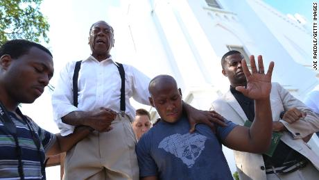 A pastor leads a group in emotional prayer after the masscare inside a Charleston church.