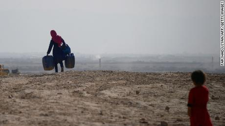 A girl carries empty containers to collect water in Sakhi village on the outskirts of Mazar-i-Sharif, in northern Afghanistan, on July 19.