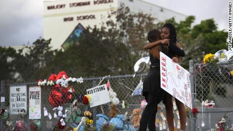 Tyra Heman, right, a senior at Marjory Stoneman Douglas High School, is hugged by Rachael Buto in front of the school where 17 people were killed on February 14 in Parkland, Florida.