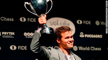 Carlsen poses with the FIDE world chess championship trophy