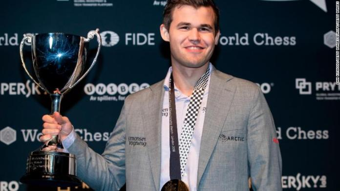 Carlsen holds his trophy up after beating Fabiano Caruana to regain his World Chess Championship title on November 28, 2018 in London.