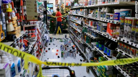 An employee walks past a damaged aisle in an Anchorage store after the earthquake.