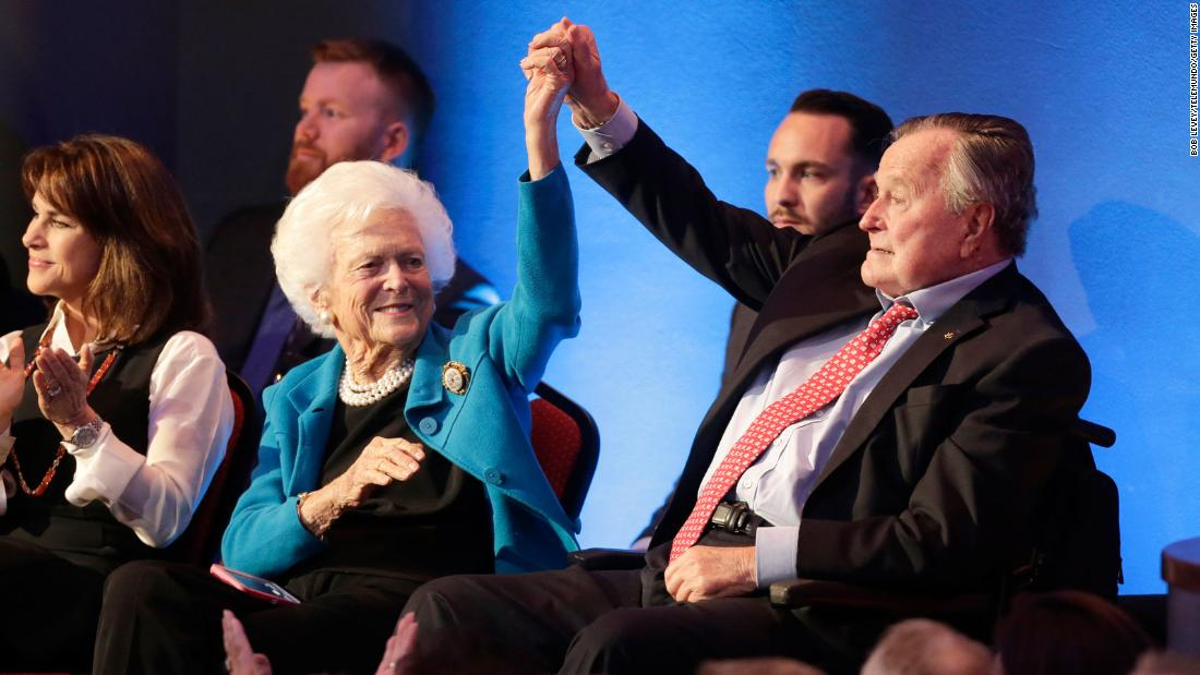 Bush holds up his wife's hand at a Republican presidential debate in 2016. Their son, former Florida Gov. Jeb Bush, was among the candidates in the debate.
