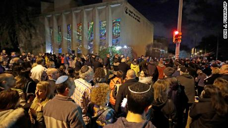 A crowd gathers outside the Tree of Life Synagogue on Sunday, the first night of Hanukkah.