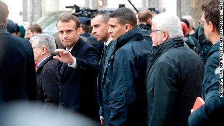 French President Emmanuel Macron waves as he leaves the Cafe Belloy, near the Arc de Triomphe in Paris on Sunday.