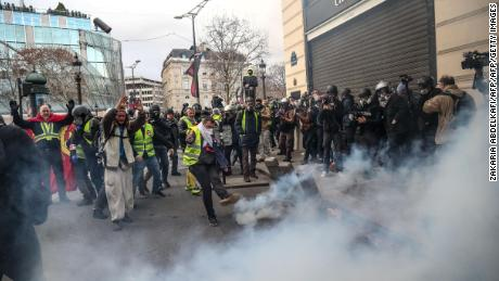 Protesters clash with riot police amid tear gas Saturday on the  Champs-Élysées in Paris.