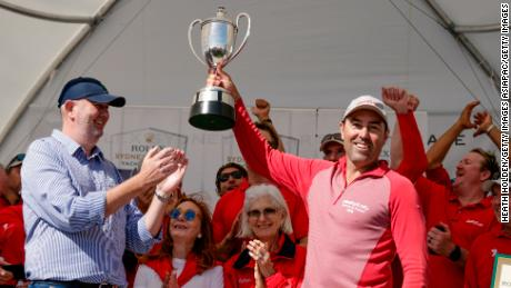 Wild Oats XI skipper Mark Richards holds the trophy aloft after taking a ninth line honors title in the 2018 Sydney to Hobart yacht race.