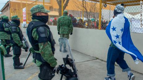Ein Mann, der in eine honduranische Nationalflagge gehüllt ist, geht am 10. Februar vor einem Schutz für zentralamerikanische Migranten in Piedras Negras, Mexiko, an einer Kette Militärpolizisten vorbei.