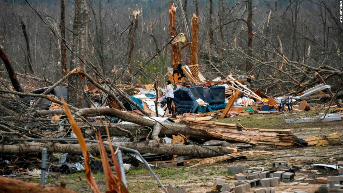 Brittney Downs looks through the debris of a family member's destroyed home in Beauregard.