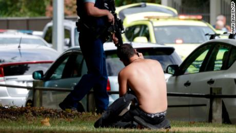 A man rests on the ground as he speaks on his mobile phone across the road from mosque in central Christchurch, New Zealand, Friday, March 15, 2019. A witness says a number of people have been killed in a mass shooting at a mosque in the New Zealand city of Christchurch; police urge people to stay indoors. (AP Photo/Mark Baker)